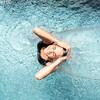 Frau unter Wasserfall im Spa Pool