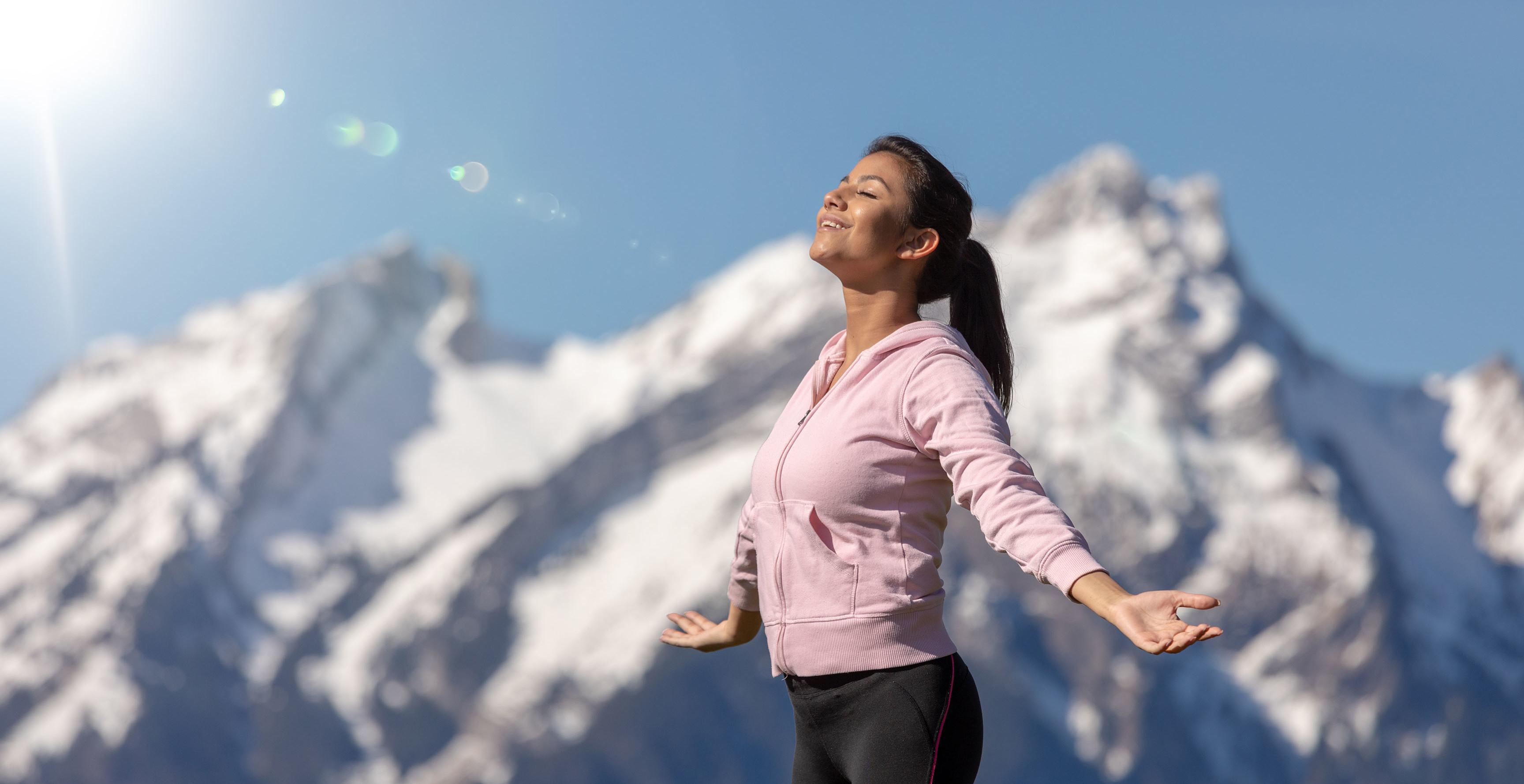 Frau genießt Sonnenstrahlen in den Alpen