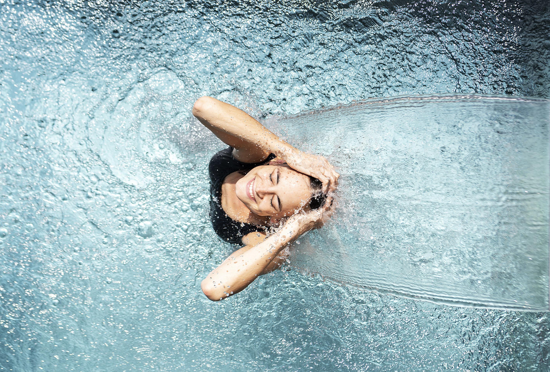 Frau unter Wasserfontäne im Pool