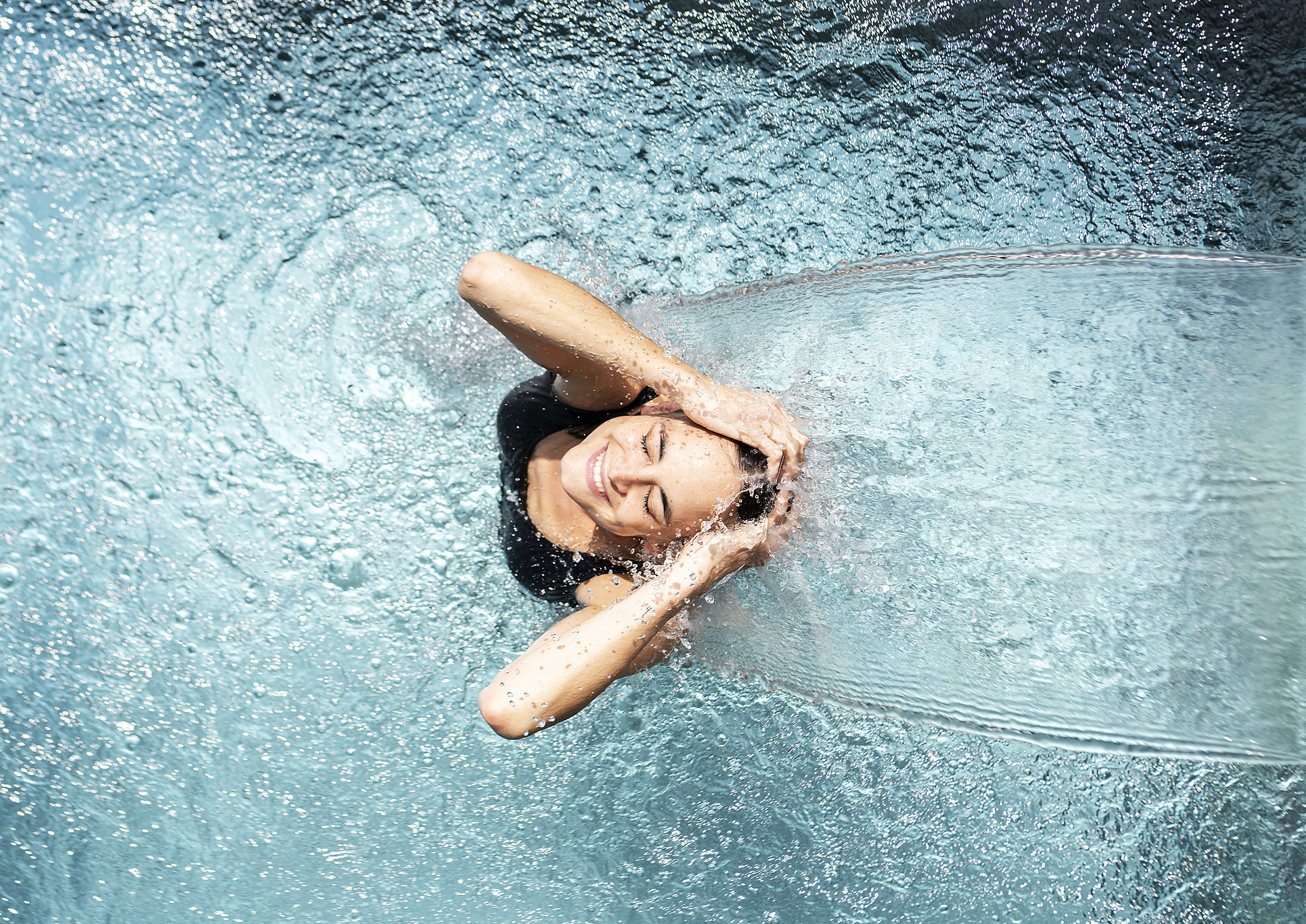 Woman under waterfountain in pool