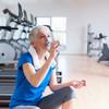 Patientin trinkt Wasser im Fitnessraum